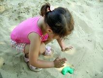 Kleines Mädchen im Sandkasten Stockbilder