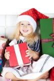 Kleines Mädchen im Sankt-Helferhut mit Geschenk Stockfotos
