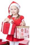 Kleines Mädchen im Sankt-Hut mit Geschenken auf Weiß Stockfotografie