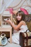 Kleines Mädchen im Schlafzimmer, das mit einem Vogel spielt Stockbilder