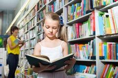 Kleines Mädchen im schulpflichtigen Alter, das mit offenem Buch steht Stockbild
