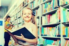 Kleines Mädchen im schulpflichtigen Alter, das mit offenem Buch steht Lizenzfreie Stockfotografie