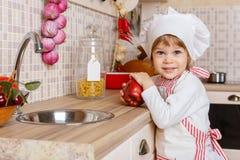 Kleines Mädchen im Schutzblech in der Küche. Lizenzfreies Stockfoto