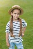 Kleines Mädchen im Strohhut, der mit der Hand auf Taille steht und Kamera im Park betrachtet Lizenzfreie Stockbilder