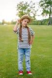 Kleines Mädchen im Strohhut, der mit der Hand auf Taille steht und Kamera im Park betrachtet Stockbilder