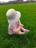 Kleines Mädchen im Strohsonnenhut, der im Gras am Park sitzt Lizenzfreies Stockfoto