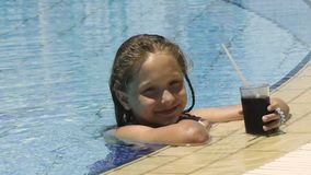 Kleines Mädchen im Swimmingpool mit kaltem Getränk stock footage