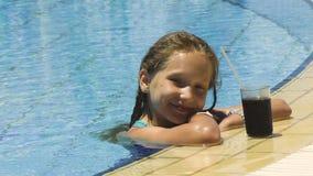 Kleines Mädchen im Swimmingpool mit kaltem Getränk