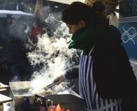 Kleines Mädchen im weißem Koch-Anzug und -hut mit großer Metalleintopfgerichtwanne Stockfoto
