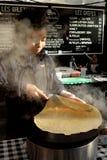 Kleines Mädchen im weißem Koch-Anzug und -hut mit großer Metalleintopfgerichtwanne Stockfotografie