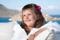 Kleines Mädchen im weißen Bademantel, der auf Terrasse sich entspannt Lizenzfreie Stockfotografie