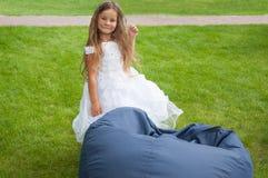 Kleines Mädchen im weißen Kleid, Braut, Sitzsack, glücklich Stockfotografie
