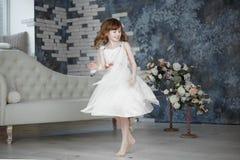 Kleines Mädchen im weißen Kleid dansing und ziehen um stockbild