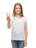 Kleines Mädchen im weißen T-Shirt, das Friedensgeste zeigt Stockfotos