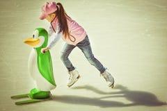 Kleines Mädchen im Winter kleidet den Eislauf auf Eisbahn Stockfoto