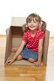 Kleines Mädchen innerhalb eines Papierkastens Stockbilder