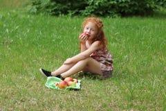 Kleines Mädchen isst Apfel auf Rasen in der grünen Sommergleichheit Lizenzfreies Stockfoto