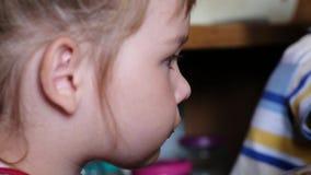 Kleines Mädchen isst ein Sandwich mit Butter und täuscht Nahaufnahme stock footage