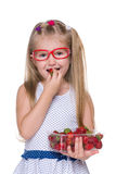Kleines Mädchen isst Erdbeere stockfotografie