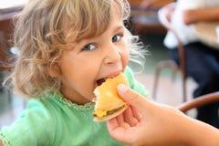 Kleines Mädchen isst Hamburger von der Hand der Mutter stockbilder