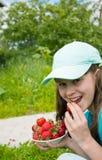 Kleines Mädchen isst reife Erdbeere Stockbild