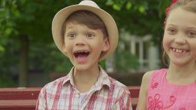 Kleines Mädchen küsst Junge ` s Backe auf der Bank stock footage