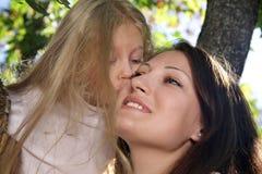 Kleines Mädchen küsst zart Mutter Stockbild