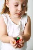 Kleines Mädchen kaut die Süßigkeiten Stockfotos