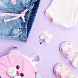 Kleines Mädchen kleidet flache Lage der Sammlung mit T-Shirt, Jeans, Sandalen, Rucksack auf Pastellhintergrund Lizenzfreies Stockfoto