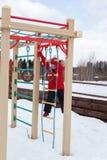 Kleines Mädchen klettert onplayground Stockbilder