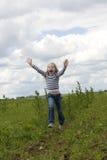 Kleines Mädchen läuft auf Wiese mit den steigenden Händen Stockfotos