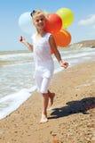 Kleines Mädchen läuft entlang die Küstenlinie mit Ballonen Stockbild