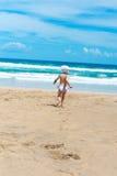 Kleines Mädchen läuft heraus zum Meer auf dem Sand lizenzfreie stockfotografie