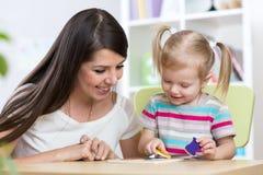 Kleines Mädchen löst Puzzlespiel Mutter, die an ihren Aktionen aufpasst lizenzfreie stockbilder