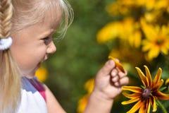Kleines Mädchen lacht und reißt ein Blumenblatt von einer gelben Gänseblümchenblume auseinander stockfotos