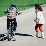 Kleines Mädchen laufen zum kleinen Jungen auf Fahrrad Stockbilder
