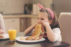 Kleines Mädchen lehnt ab, Frühstück zu essen stockfotos