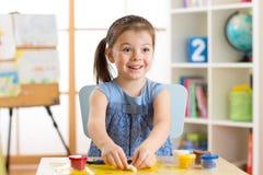 Kleines Mädchen lernt, bunten Spielteig im Kinderraum zu benutzen Lizenzfreie Stockbilder