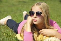Kleines Mädchen liegt auf dem Gras mit Gläsern lizenzfreie stockfotografie