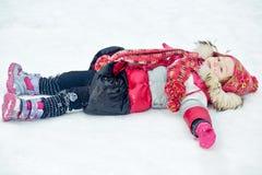 Kleines Mädchen liegt auf Schnee mit den Händen, die zu den Seiten ausgedehnt werden stockbilder