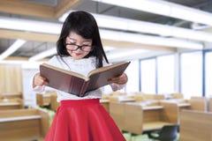 Kleines Mädchen liest Buch in der Klasse Lizenzfreie Stockfotos