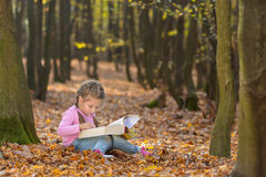 Kleines Mädchen liest ein Buch Stockfotografie