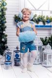 Kleines Mädchen LSmiling, das neben einem Weihnachtsbaum und einem Christus steht Stockfoto