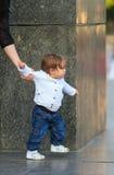 Kleines Mädchen macht die ersten unabhängigen Schritte, die Griffmutterhand sind Stockfoto
