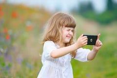 Kleines Mädchen macht Foto mit der Handykamera, die herein im Freien ist Lizenzfreie Stockfotos