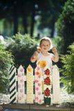 Kleines Mädchen malt einen Zaun Stockbilder