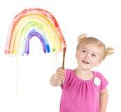 Kleines Mädchen malt Regenbogen auf Fenster Stockbild