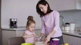 Kleines Mädchen in mischendem Mehl des rosa Hemdes in der Schüssel mit ihrer Mutter auf ihrer Küche Zusammen kochen, backend mit  stock video footage
