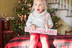 Kleines Mädchen mit überraschtem Blick auf ihrem Gesicht an der Weihnachtszeit Stockfoto