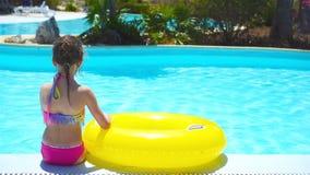 Kleines Mädchen mit aufblasbarem Gummikreis im Swimmingpool stock video